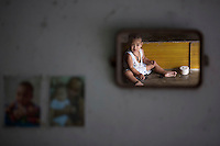 A child is reflected in the mirror in home of a barber in Ban Nam Khem December 13, 2014. Therasak, a local barber who survived 2004 tsunami with his family members returned to the village soon after disaster but says his 22 year old daughter still suffers from tsunami related illness. Ban Nam Khem, a small fishing village on Thailand's Andaman Sea coast, lost nearly half its 5,000 people in tsunami on December 26, 2004. Thailand prepares to mark the tenth anniversary of 2004 tsunami, the deadliest on the record, that killed at least 226,000 people in 13 Asian and African countries. In Thailand, over 5300 people were killed, including several thousand foreign tourists, when the waves swamped six coastal provinces, turning some of the world's most beautiful beaches into mass graves.  REUTERS/Damir Sagolj (THAILAND)