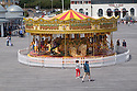 "a view of the merry-go-round from the 'top deck' of Hastings Pier, looking back towards land. The pier has recently (April 2016) been reopened after extensive rebuilding owing to a fire razing it to the ground in 2010. The council compulsorily purchased it from its owners in 2012, and the so-called ""people's pier"" is now in the hands of the Hastings Pier Charity and more than 3,000 shareholders, who bought into the project at £100 a share."