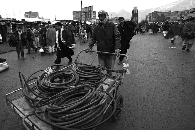 A man pushes a cart loaded with coils of rubber hose in the central market of Kabul, Afghanistan. Despite the ever-present mud and miserable winter weather, the market bustles daily with commerce of all kinds. Taliban attacks in the Afghan capital have so far been infrequent, and as life goes on at a normal pace, the war often seems far away. Feb. 3, 2009.