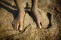 The feet of a child worker at Bhollar Ghat. At least 10,000 people, including 2,500 women and over 1,000 children, are engaged in stone and sand collection from the Bhollar Ghat on the banks of the Piyain river. Building materials such as stone and sand, and the cement which is made from it, are in short supply in Bangladesh, and commands a high price from building contractors. The average income is around 150 taka (less than 2 USD) a day.