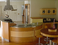 The curved lines of this horseshoe-shaped kitchen with stainless steel work surfaces and marquetry detailing are echoed in the surrounding furniture