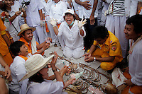 People react around unclaimed human remains taken out of grave during a Thai Chinese ceremony at the Mang Teung Sua Jung Cemetery in Chonburi province southeast of Bangkok March 18, 2012. Every 10 years, hundreds of people wearing white, a customary colour for funerals and visiting temples, gather at this cemetery to exhume and cremate corpses as they believe they are helping the dead who have no friends or relatives. The ashes of the unclaimed bodies are spread on the sea to make room at the burial ground for more unclaimed bodies in the coming years. The tradition originated 90 years ago after diseases like Malaria killed many Thais of Chinese descent living in Chonburi.  REUTERS/Damir Sagolj (THAILAND)