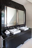 In the master bathroom two washbasins with mirrors above are set in a bespoke bronze tile surround.