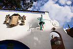 "Portmeirion, in North Wales, is a resort, where no one has ever lived. A self-taught Welsh architect named Sir Clough Williams-Ellis built it out of architectural salvage between the 1920s and 1970s, loosely based on his memories of trips to Portofino. Including a pagoda-shaped Chinoiserie gazebo, some Gothic obelisks, eucalyptus groves, a crenellated castle, a Mediterranean bell tower, a Jacobean town hall, and an Art Deco cylindrical watchtower. He kept improving Portmeirion until his death in 1978, age 94. It faces an estuary where at low tide one can walk across the sands and look out to sea. At high tide, the sea is lapping onto the shores. Every building in the village is either a shop, restaurant, hotel or self-catering accomodation. The village is booked out at high season, with numerous wedding receptions at the weekends. Very popular amongst the English and Welsh holidaymakers. Many who return to the same abode season after season. Hundreds of tourists visit every day, walking around the ornamental gardens, cobblestone paths, and shopping, eating ice-creams, or walking along the woodland and coastal paths, amongst a colourful assortment of hydrangea, rhododendrons, tree ferns and redwoods. The resort boasts two high class hotels, a la carte menus, a swimming pool, a lifesize concrete boat, topiary, pools and wishing wells. The creator describes the resort as ""a home for fallen buildings,"" and its ragged skyline and playful narrow passageways which were meant to provide ""more fun for more people."" It does just that.///Detail ornamental decorations, a bell and coat of arms, heraldry. Near prisoner bookshop."