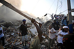 Residents run in and out of a destroyed store to get goods in downtown Port-au-Prince after the major  earthquake in Haiti on January 18, 2010.