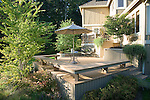 A sunny, summer scene of a raised, multi level residential deck constructed of Trex brand composite decking on a sloping lot in a suburb near Seattle, WA.  Design by Sander Groves Landscapes, Inc.
