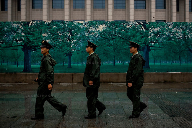 Military police officers march past a fenced area in downtown Beijing, China on Sunday, August 10, 2008.  Kevin German
