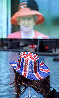 A tourist,wearing a Union Jack hat watches a large TV screen in Trafalgar Square showing an image of Queen Elizabeth the Second of Britain, during the Golden Jubilee celebration in London. England, United Kingdom July 2002