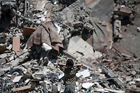 "August 26, 2014 - Gaza City, Gaza strip, Palestinian Territory: A Palestinian child looks at the rubble of an apartment complex buildiing after it was targeted by an airstrike night raid in central Gaza City as ""Protective Edge"" Israeli military operation continues in the Gaza strip. (Narciso Contreras/Polaris)"