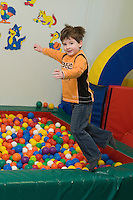 Happy Caucasian Kid Boy Jumping into  Playground Toy Balls