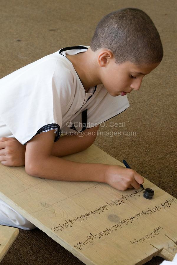 Zliten, Libya. Boy Writes Verses from the Koran on his Prayer Board.  He studies to memorize the Koran, working under the supervision of a teacher, or muqri.
