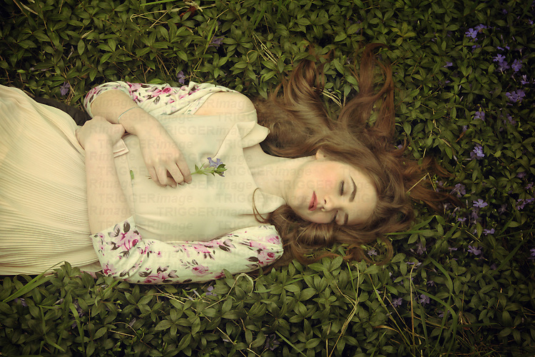 A young girl with blond hair and pale skin dressed in a beige dress lying on a bed of grass and purple flowers