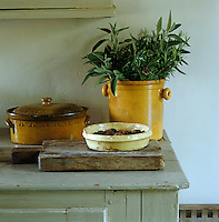A pot of fresh herbs together with other rustic  ceramic vessels on the edge of a painted dresser