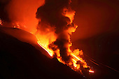 Nighttime paroxysmal eruption of Mount Etna Volcano, Italy, 2012. Steam cloud rising as lava melts snow in Valle del Bove.
