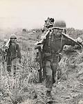 Heavy going for this Leatherneck machine gunner as he struggles up a hill on Guam carrying the tripod for his weapon. Behind him, his partner carries the barrel while the others tote the ammo.