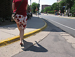 A woman walks from the street to a sidewalk during the lunch hour.  She is wearing a flowery summer dress with matching top.