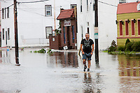 MAMARONECK, NY - AUGUST 28: A local resident negotiates high water on flooded Mamaroneck Avenue in the Village of Mamaroneck, New York on Sunday August 28, 2011 in the aftermath of Hurricane Irene.
