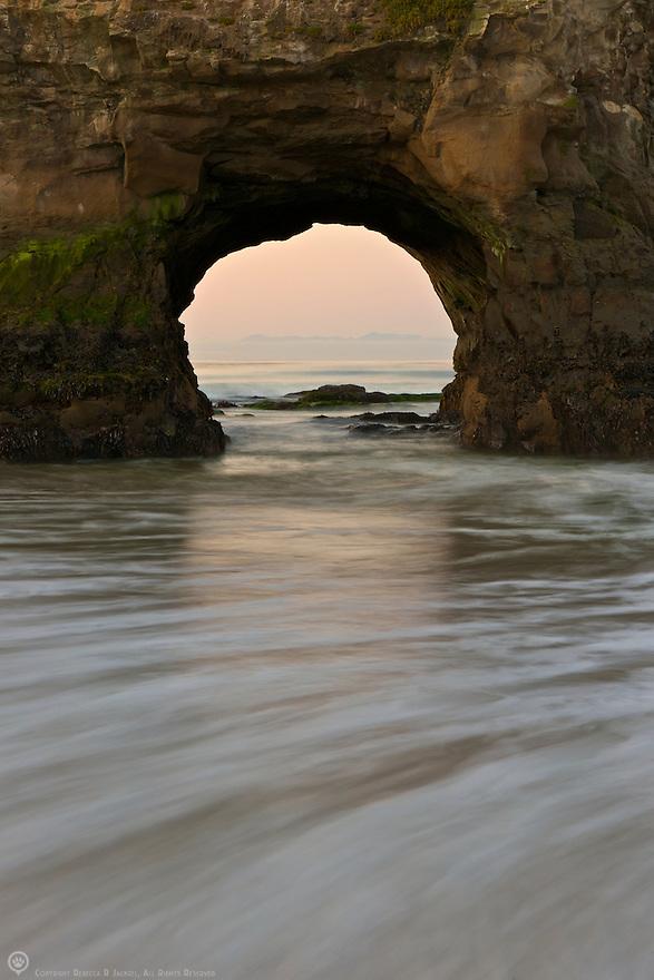 Sunrise through the arch at Natural Bridges State Beach, Santa Cruz, California