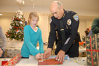 "Santa Monica Police  Chief Timothy J. Jackman and Amanda Reymer, 12, wrap a gift at Santa Monica Place during the  'Its a Wrap Party' on Thursday, December 16, 2010...Community leaders, volunteers from the Police Activities League (PAL), Bayside District Corporation and Santa Monica Place, wrapped more than 250 gifts which were collected during the Winterlit ""Best Gift Ever"" community gift drive. Gifts collected will be distributed this Saturday at PAL to children who might otherwise go without presents."