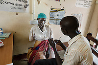 "N. Uganda, Gulu District. Joshua Tugumisirize, a visiting PCAF psychiatrist & Freddy Odong, a PCAF nurse, perform a psychiatric assessment and counseling at the local rural clinic in Gulu. ""Ruth"" lost her arm during the war and struggles with depression. She has no husband but a young son helps her. ""Ruth"" walks many miles to come to the rural clinic where she gets periodic counseling & treatment. It took nearly an hour just to drive to her home."