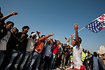 Waving a US flag, African asylum-seekers protest in front of the US Embassy in Tel Aviv, Israel, calling the US to help them receive recognition from the Israeli government as refugees.
