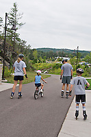 A family exercises together on a biking and walking path in Marquette Michigan.