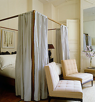 Soft grey silk curtains frame the simple wooden four-poster bed with one of a collection of watercolours by Mats Gustafson on the wall behind it