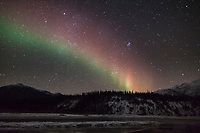 Dim but colorful aurora borealis and starry night sky over the Koyukuk river in Alaska's Brooks range.