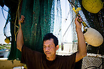From left, Hung Tran, 42, waits to ship off  on the H&R shrimp boat at Dean Blanchard Seafood, Inc. in Grand Isle, LA on June 24, 2010 where a fishing ban has been put in place due to the B.P. oil spill. The H&R crew will head west in hopes to find open fishing waters after waiting two months for B.P. to hire their boat.
