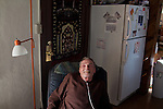 Medical marijuana in New Mexico.  ..Medical marijuana patient Robert Jones at his Las Vegas, New Mexico home.  After cancer treatments drained his savings, Jones became eligible for Section 8 housing.  Although open with the city, police, and his landlord, the county recently moved to terminate his Section 8 benefits because of his ongoing marijuana use.  After hearing testimony from Jones, his pastor, a city council-member, his doctor, and other community advocates, county commissioners decided to reinstate his benefits.  ..Jones received a medical marijuana patient card during his cancer treatments and continues to use marijuana for ongoing symptomsincluding appetite loss and depression.  Jones' cancer is currently in remission.  New Mexican law is extremely convoluted and provides only 11 licensed growers for the entire state.  State regulations on the matter continue to conflict with federal drug laws, making the matter evermore confusing...Also pictured is Jones' caregiver, Bill Emerick.  Emerick works with Jones for 45 hours per week, helping him with his chores, cleaning, medications, and marijuana cultivation. .. 1.  Photographer Name: Matt Slaby. 2.  Agency Name: LUCEO.~. 4.  Model Released: Yes . 5.  AARP Rights or Restrictions: None. 6.  AARP Contract #: 5174. 7.  AARP Assigning editor and business unit or publication: Wichita/Bulletin