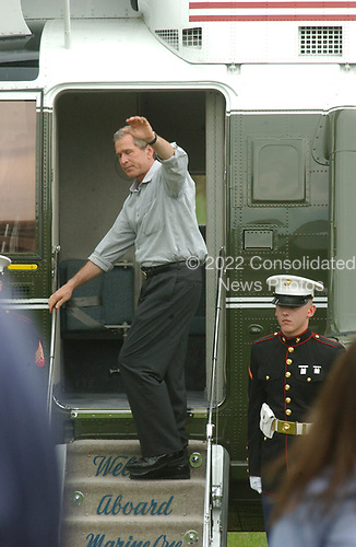 United States President George W. Bush waves as he boards Marine One to depart the James J. Rowley Training Center in Beltsville, Maryland as he heads to Camp David, the presidential retreat near Thurmont, Maryland after his tour of the facility on April 19, 2002.<br /> Credit: Ron Sachs / CNP