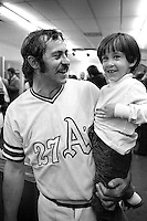 Oakland Athletics pitcher Jim &quot;Catfish&quot; Hunter holding his son Paul in the locker room after the A's had just beaten the Cincinnati Reds in the 1972 World Series.<br />