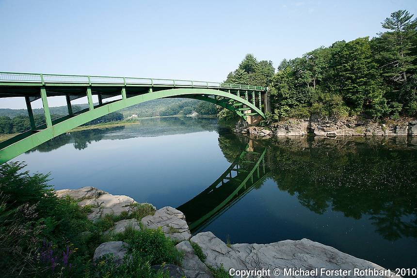 A bridge crosses the Upper Delaware River at Narrowsburg, NY. The Upper Delaware Scenic and Recreational River, part of the National Park Service's Wild and Scenic Rivers System, stretches 73.4 miles along the New York - Pennsylvania border.<br /> <br /> Hydraulic fracturing or &quot;fracking&quot; is new method of drilling for natural gas: millions of gallons of water, sand and proprietary chemicals are pumped down a well under high pressure. The pressure fractures the shale, opening fissures so that natural gas can flow more freely. In August 2010, fracking is being widely used in the Marcellus Shale formation under Pennsylvania while New York considers a moratorium until the environmental effects can be reviewed. <br /> <br /> The 2005 Energy Policy Act exempted natural gas drilling from the Safe Drinking Water Act (plus some regulations of the Clean Water Act and Clean Air Act), and exempts companies from disclosing the chemicals used during fracking. Scientists have identified volatile organic compounds (VOCs) such as benzene, ethylbenzene, toluene, methane and xylene that have been found in contaminated drinking water near drilling sites. Other environmental concerns include surface water contamination, air pollution, forest fragmentation, plus human health problems. On the other hand, gas companies and property owners stand to earn up to one trillion dollars in profits from drilling in the Marcellus Shale.<br /> <br /> &copy; Michael Forster Rothbart<br /> www.mfrphoto.com <br /> 607-267-4893 o 607-432-5984<br /> 5 Draper St, Oneonta, NY 13820<br /> 86 Three Mile Pond Rd, Vassalboro, ME 04989<br /> info@mfrphoto.com<br /> Photo by: Michael Forster Rothbart<br /> Date: 8/2010    File#:  Canon 5D digital camera frame 68778