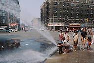 Brooklyn, New York City, NY - August, 1971. <br /> A classic and charming New York summer scene: To keep the children cool during the dog days of August, the firemen are opening the fire hydrant. <br /> Brooklyn, New York City, NY. Aout, 1971. <br /> Vue classique et touchante des ghettos New Yorkais. Les jours de grande chaleur, les pompiers ouvre les vannes des bornes d&rsquo;incendies pour la grande joie des enfants.