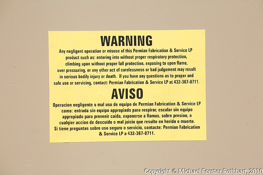 This view shows a warning sign posted at a natural gas well pad in Dimock, PA, run by Cabot Oil &amp; Gas Corporation. Overall, about 200 gas wells have been drilled in Dimock in the past two years; Pennsylvania had over 77,000 wells as of 2009. <br /> <br /> Hydraulic fracturing or &quot;fracking&quot; is new method of drilling for natural gas: millions of gallons of water, sand and proprietary chemicals are pumped down a well under high pressure. The pressure fractures the shale, opening fissures so that natural gas can flow more freely. In August 2010, fracking is being widely used in the Marcellus Shale formation under Pennsylvania while New York considers a moratorium until the environmental effects can be reviewed. <br /> <br /> The 2005 Energy Policy Act exempted natural gas drilling from the Safe Drinking Water Act (plus some regulations of the Clean Water Act and Clean Air Act), and exempts companies from disclosing the chemicals used during fracking. Scientists have identified volatile organic compounds (VOCs) such as benzene, ethylbenzene, toluene, methane and xylene that have been found in contaminated drinking water near drilling sites. Other environmental concerns include surface water contamination, air pollution, forest fragmentation, plus human health problems. On the other hand, gas companies and property owners stand to earn up to one trillion dollars in profits from drilling in the Marcellus Shale.<br /> <br /> &copy; Michael Forster Rothbart<br /> www.mfrphoto.com <br /> 607-267-4893 o 607-432-5984<br /> 5 Draper St, Oneonta, NY 13820<br /> 86 Three Mile Pond Rd, Vassalboro, ME 04989<br /> info@mfrphoto.com<br /> Photo by: Michael Forster Rothbart<br /> Date: 8/2010    File#:  Canon 5D digital camera frame 68950.