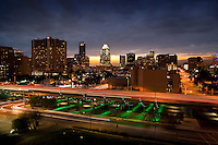 Sunset falls on the downtown Austin Skyline as the I-35 Makeover Project Parking garage performs its colored light show in green.