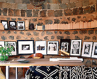 A collection of black and white photographs is offset by the rough stone walls in the living room