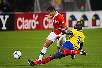Segundo Castillo (14) of Ecuador goes in on  a tackle on Alexis Sanchez (7) of Chile. Ecuador defeated Chile 3-0 during an international friendly at Citi Field in Flushing, NY, on August 15, 2012.