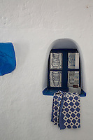 The frame of this small recessed window in a whitewashed wall has been painted a royal blue