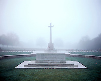 Fog envelopes a memorial cross in the Hooge Crater Commonwealth War Cemetery where almost 6,000 men, killed in the Ypres Salient during World War I, are laid to rest.