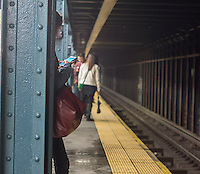 While waiting for the subway at the West 28 St. subway station in New York, a commuter uses her smartphone on Thursday, May 8, 2014. (© Richard B. Levine)