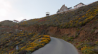 The road to Point Sur Light Station climbs slowly up the edge of the hill the station is built on.  Here the majority of the buildings of the station are visible overlooking the ocean (which is to camera-left).  Buildings visible include the blacksmith shop, barn, water tower, assistant keeper's house, and head keeper's house (from left to right).
