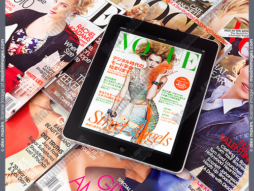 Apple iPad 3G tablet with an electronic issue of Vogue lying on top printed fashion magazines