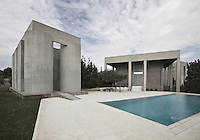 The area around the swimming pool has been paved with stone slabs, matching the stark palette of the concrete buildings