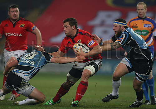 01.12.2012 Limerick, Ireland. CJ Stander is tackled by Peter Horne, during the RaboDirect PRO12 game between Munster and Glasgow Warriors from Thomond Park.
