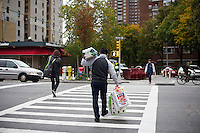 "A shopper with groceries and bottled water leaves a convenience store prior to Hurricane Sandy in Chelsea in New York on Sunday, October 28, 2012. In advance of the arrival of Hurricane Sandy New York will down the subways at 7 PM on Sunday and evacuate low lying ""Zone A"" areas including Battery Park City. In addition the schools will be closed on Monday. (© Frances M. Roberts)"