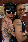 Lesbian lovers with tattoos Looking at the camera at S&M Street Fair.