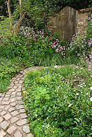 Stone garden bench in rustic country garden full of old-fashioned heirloom flowers, stone pavers in curving pathway, wide view
