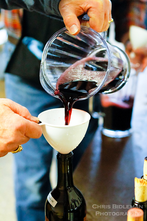 The art of double decanting red wines during a wine judging festival requires the wine to first be poured into a pitcher and then funnelled back into the original bottle.  As seen during the Savor NW 2014 wine awards, Cannon Beach, OR