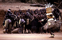 Vhawhera initiate masked in grass and reed dances before female intiates in the stockaded capital of the Lobedu people, ha-Modjadji, South Africa. (Greg Marinovich) horizontal colour slide.